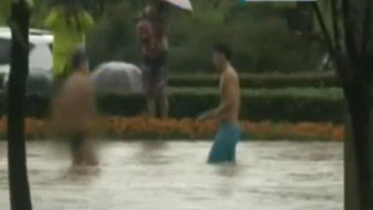暴雨后小伙把马路当泳池 想红?别拿安全当筹码